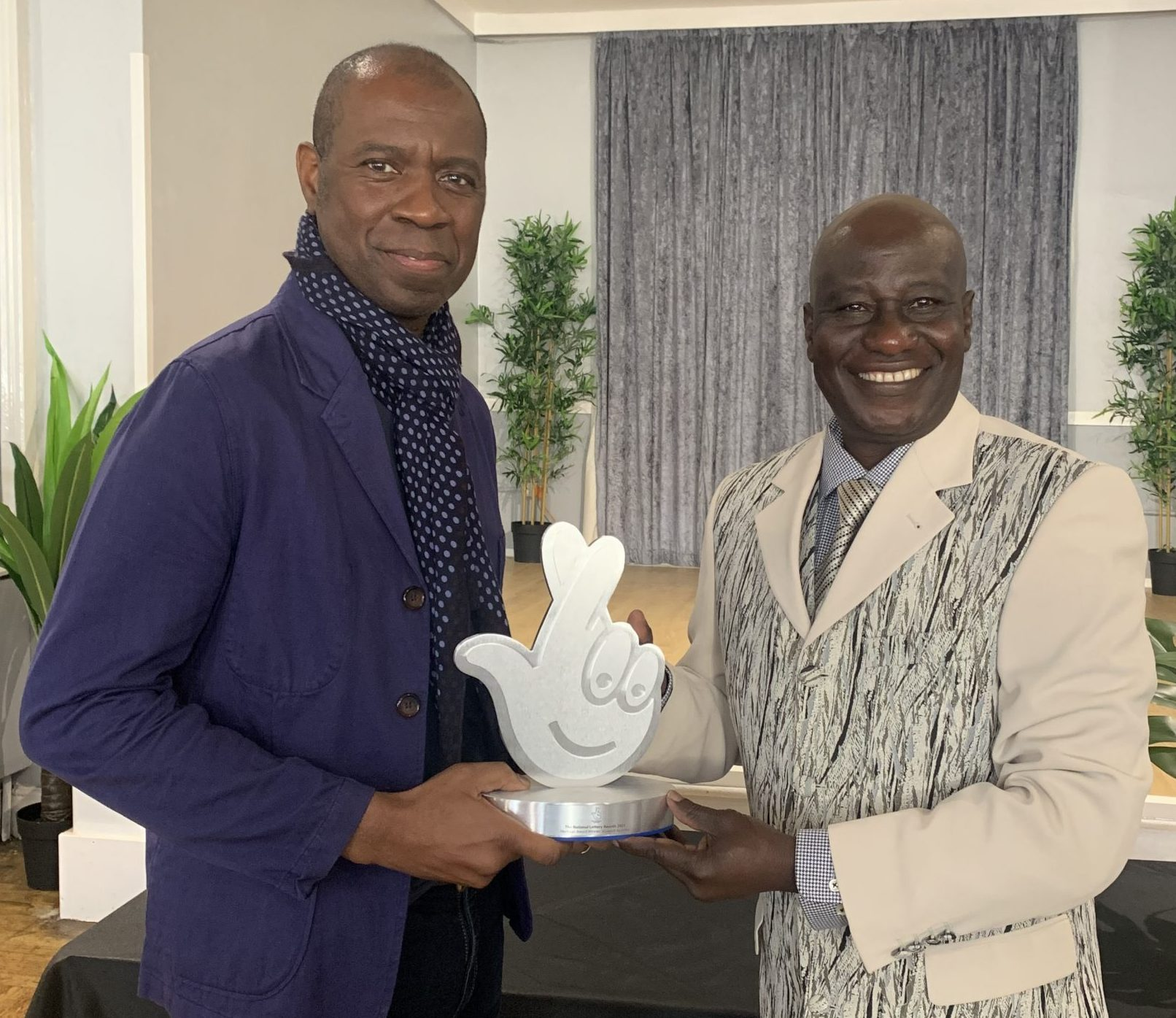 SEM's Maxwell Ayamba Accepts award from BBC Presenter Clive Myrie